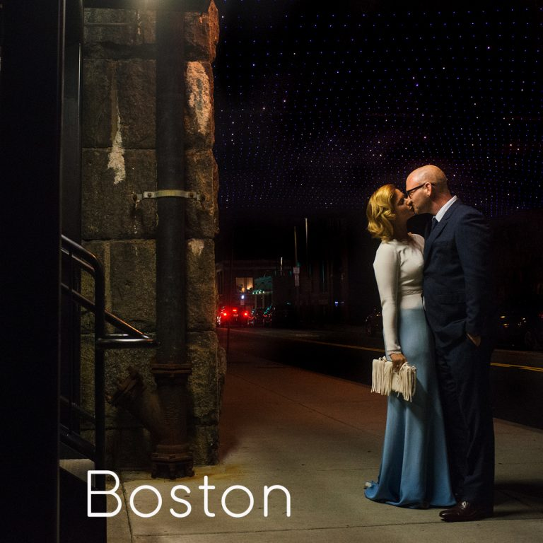 bride and groom kissing at night on a street in Boston
